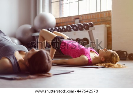 Two young adult women doing pelvic muscle exercises on individual rectangular mats with weights and stability ball in background at gym