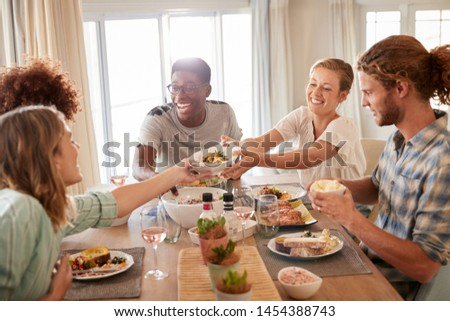 Two young adult women passing a dish across the dinner table during lunch with friends, close up