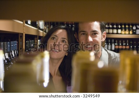 Two young adults looking at wine bottles