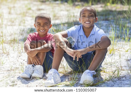 Two young African American boy children sitting together in the summer sunshine