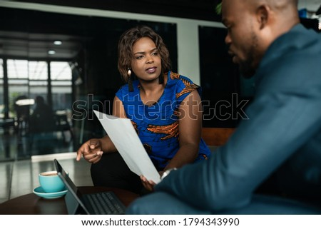 Two young African businesspeople discussing paperwork during a casual meeting together in an office lounge