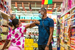 Two young Africans wearing face mask for protection,shopping in a supermarket, greeting each other with elbow, practicing social distancing - Black millennial healthy lifestyle in covid-19 pandemic