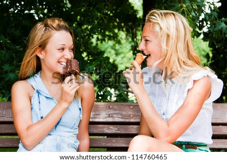 Two young and beautiful woman eating ice cream on a bench in the park