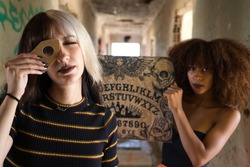 two young and beautiful women, one blonde and one African-American, doing the Ouija board in a corridor of an abandoned building. The women are invoking the spirits of the afterlife.
