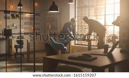 Two Young and Handsome Designers Sit on the Desk and Discuss Social Media App Interfaces on Their Laptops. They Work in a Sunny Creative Office Loft with a Big Window View on Modern Urban City.