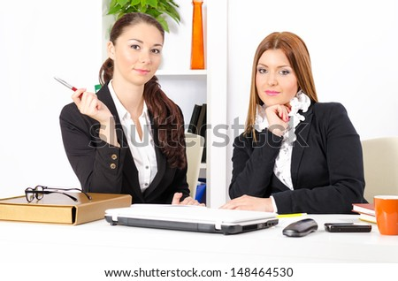 Two young and pretty businesswomen in their office working together