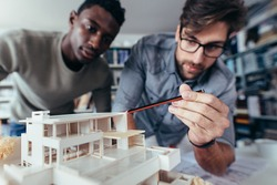 Two young architects working on new architectural house model. Designers looking at house model in studio.