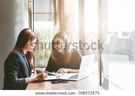 Two young asia business woman working together in office space