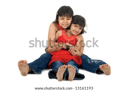 Two young Asian girls showing sisterly affection and smiles