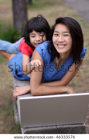 Two young Asian sisters happy outdoors with a laptop computer on a bench