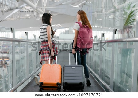 Two young asian  woman traveler with backpack walking to the gate in the airport,Backpacker concept.