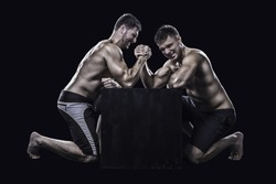 Two young athletes have a hard arm wrestling match on a black box shirtless