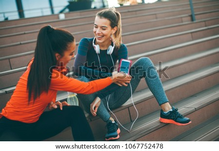Two young attractive female runner taking break after jogging outdoors #1067752478