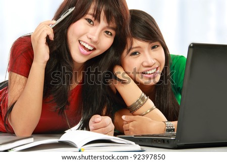 two young attractive female student smiling looking to the camera - stock photo