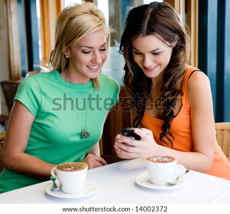 Two young attractive women drinking coffee at a restaurant and looking at phone