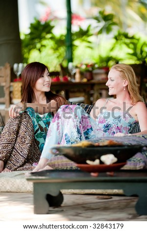 Two young attractive women having lunch and drinks on vacation