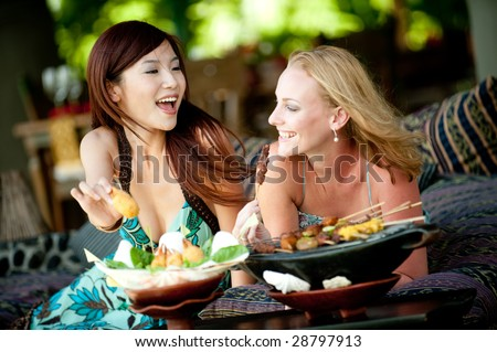 Two young attractive women having lunch on vacation