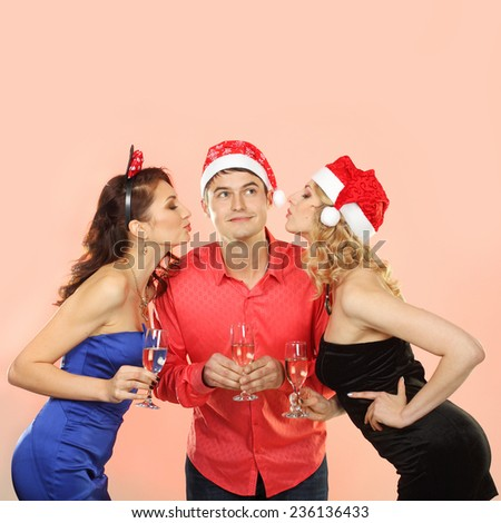 Two young attractive women kissing man. company enjoys Christmas.  Portrait of modern young people enjoying themselves at Christmas party.