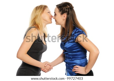 Two young attractive women shake hands and look at each other. Isolated on white.