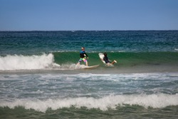 Two young australian surfers have fun riding the waves at  Maroubra beach, Sydney, Australia.