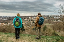 Two young backpackers enjoying view of Prague city skyline and Prokop valley,Czech Republic.Attractive landscape with deep valley,hiking trails,Prague panorama in background.Active citylife style