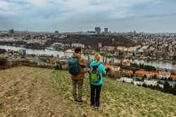 Two young backpackers enjoying view of Prague city skyline and Vltava river,Czech Republic.Attractive landscape with deep valley,hiking trails,Prague panorama in background.Active citylife style.