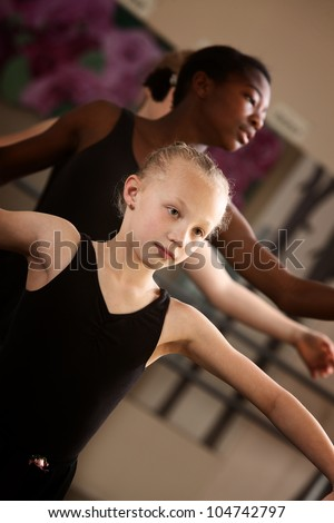 Two young ballet students concentrate in class