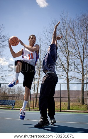 Two young basketball players compete fiercely against each other.