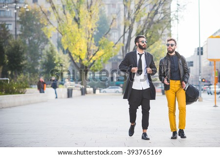 two young bearded blonde and black hair modern businessman, walking in the city backlight, one overlooking right, the other overlooking left - working, successful concept #393765169