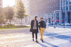 Two young bearded blonde and black hair modern businessman, walking in the city using smart phone - working, successful concept