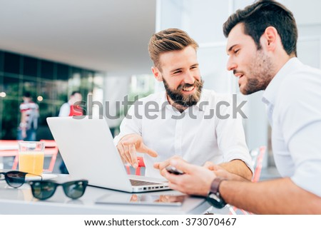 Two young bearded caucasian modern business man sitting in a bar, using laptop, looking each other, smiling and chatting - business, work, technology concept