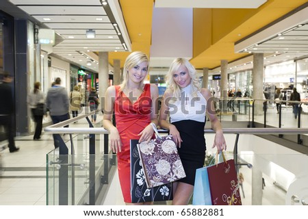 two young beautiful and elegant woman inside a commercial center go for shopping with bags