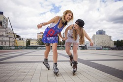 Two young beautiful blonde hipster girls on summer day having fun in european city roller-skating