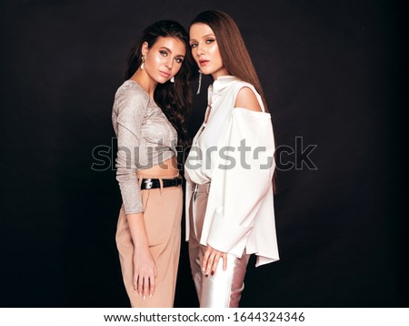 Two young beautiful brunette girls in nice trendy summer clothes.Sexy carefree women posing over black background in studio.Fashionable models with bright evening makeup