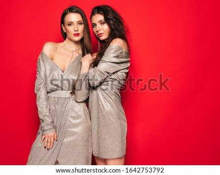 Two young beautiful brunette girls in nice trendy summer shiny dress.Sexy carefree women posing near red wall in studio.Fashionable models with bright evening makeup.They hug and touch each other
