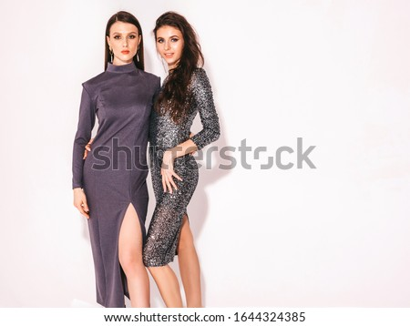 Two young beautiful brunette girls in nice trendy summer summer shiny dress.Sexy carefree women posing near white wall in studio.Fashionable models with bright evening makeup