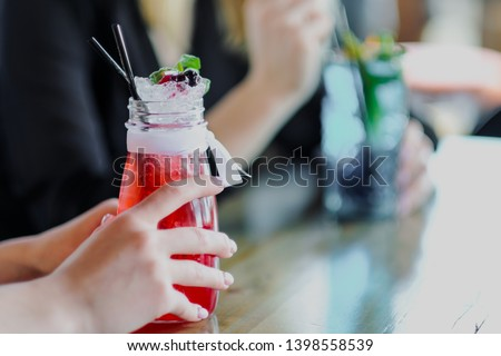 Two young beautiful girls, blonde and brunette, sit at a table in a cafe or restaurant. Communicate and talk, drink blue and red cocktails drinks. Cool drinks, lemonade. #1398558539