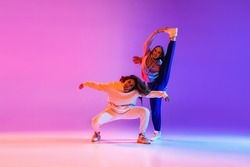 Two young beautiful girls making hip-hop tricks dancing on gradient pink purple neon background. Sport achievement, expression. Concept of dance, youth, hobby, dynamics, movement, action, ad