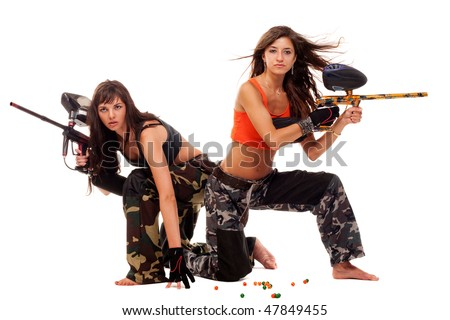 Two young beautiful girls posing like playing paintball