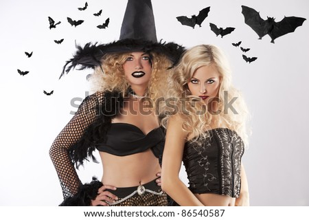 two young beautiful girls wearing witch black dress ready for black magic