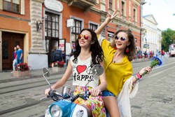two young beautiful hipster women riding on motorbike city street, summer europe vacation, traveling, smiling, happy, having fun, sunglasses, stylish outfit, adventures, positive, friends together