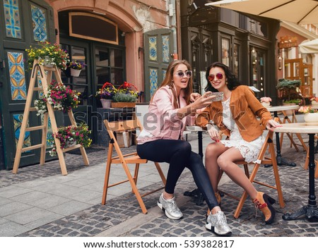 two young beautiful hipster women sitting at cafe, stylish trendy outfit, europe vacation, street style, happy, having fun, smiling, sunglasses, looking at smartphone, taking selfie photo, flirty #539382817