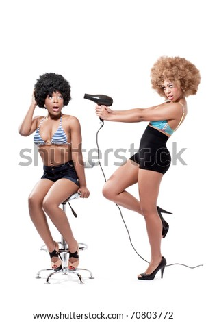 Two young beautiful pinup girls in a hairdresser salon having fun, isolated on white