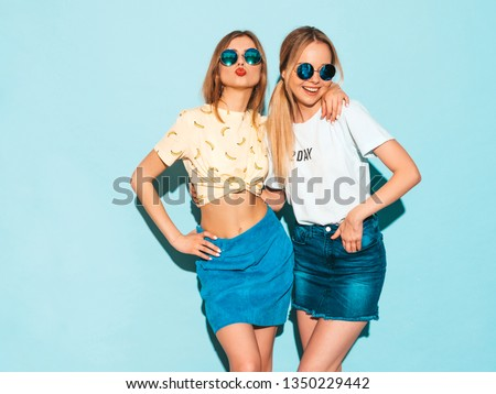 Two young beautiful smiling blond hipster girls in trendy summer colorful T-shirt clothes. Sexy carefree women posing near blue wall in round sunglasses. Positive models having fun