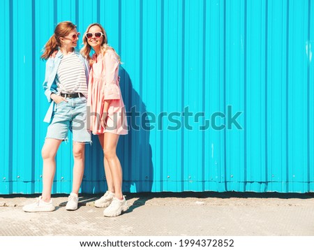 Two young beautiful smiling hipster female in trendy summer clothes and jeans.Sexy carefree women posing in the street near blue wall.Positive pure models having fun at sunset, hugging and going crazy