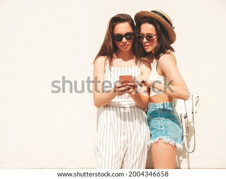 Two young beautiful smiling hipster female in trendy summer  clothes and jeans shorts.Sexy carefree women posing in the street near white wall.Positive models using smartphone apps, looking at screen