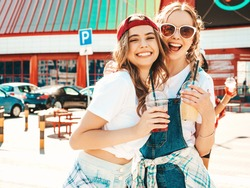 Two young beautiful smiling hipster female in trendy summer clothes.Sexy carefree women posing outdoors.Positive models holding and drinking fresh cocktail smoothie drink in plastic cup with straw