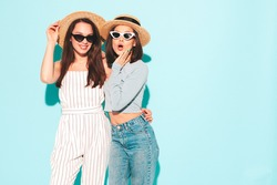Two young beautiful smiling hipster female in trendy summer  clothes.Sexy carefree women posing near light blue wall in studio.Positive and cheerful models in hats