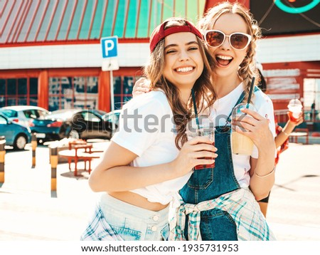 Two young beautiful smiling hipster female in trendy summer clothes.Sexy carefree women posing outdoors.Positive models holding and drinking fresh cocktail smoothie drink in plastic cup with straw Stock photo ©
