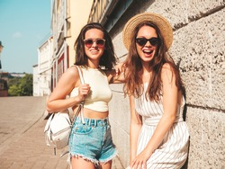 Two young beautiful smiling hipster female in trendy summer clothes.Sexy carefree women posing in the street near wall in hat. Positive pure models having fun at sunset, hugging